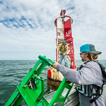 Alistair Lord (right) prepares to hand off the clamperatus to Zachary Hasdorff during their installation of the CCPORTS system off the coast of Port Aransas, Tx.